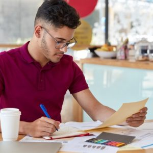 image-busy-unshaven-copy-writer-college-student-dressed-casual-clothing-makes-notes-notebook-focused-into-document-looks-attentively-poses-small-cafetiera-drinks-hot-beverage_273609-29259