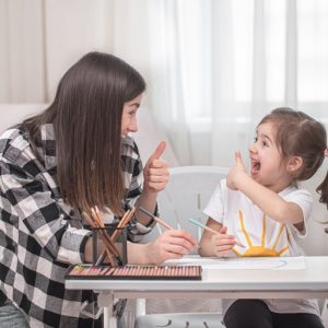 mother-with-child-sits-table-does-homework-child-learns-home-home-schooling-space-text_169016-4683